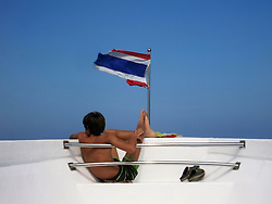 A boy relaxes at the bow of a boat sailing between Koh Phi Phi and Phuket, Thailand, Southeast Asia