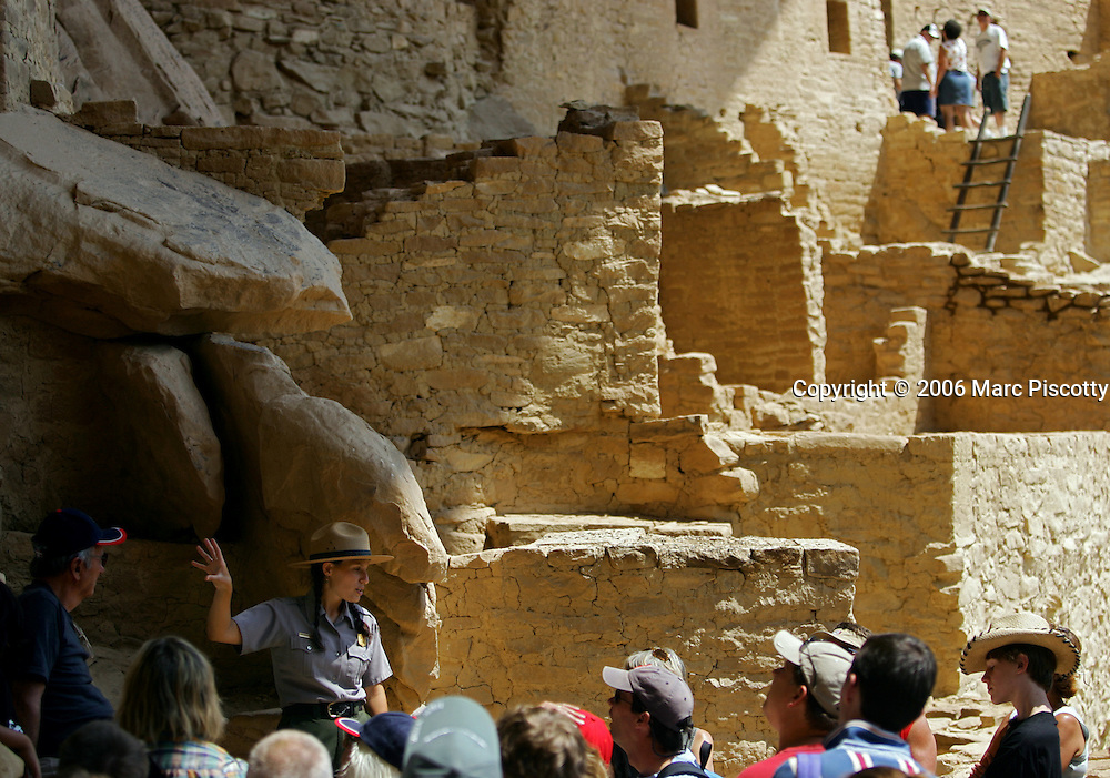 """Park Ranger Amanda Kuhnel (cq, lower left), 23, points out some of the features of the Cliff Palace dwelling during an hour-long tour at Mesa Verde National Park near Cortez, Co. on Wednesday June 28, 2006. It is Kuhnel's first year working at the park and said the National Park Service had hired additional interpretive guides in the park this summer to handle the increased number of visitors for its 100th birthday. She said, """"my tours have all been sold out"""". On June 29, 1906 Theodore Roosevelt designated Mesa Verde a national park, the first cultural national park in the history of the world. The park will celebrate it's 100th birthday with a weekend of events, dancing, musical entertainment and special tours of some of the cliff dwellings. Cilff Palace is the largest of all the dwellings at Mesa Verde with 150 rooms and 21 kivas..(MARC PISCOTTY/ © 2006)"""