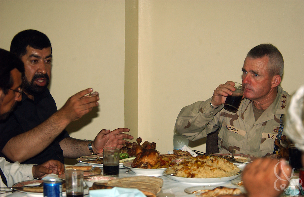 Kandahar regional governor Gul Agha Sherzai (l) hosts Coalition Joint Task Force (CJTF) 180 U.S. Commander General Dan McNeill for lunch at his home July 21, 2002 in Kandahar, Afghanistan. Sherzai had previously endorsed a plan that would require U.S. forces to seek permission of local authorities before launching military operations in the central and southern provinces of Afghanistan. Other local governors refused to back the plan, and after today's meeting with McNeill, Sherzai appears to have backed away from the idea..