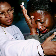 LITTLE COMFORT: Avis Ottey, above, is consoled by a friend after Adrian Kinkead was found guilty yesterday of murdering her daughters Marsha and Tamara. Kinkead received two life sentences.<br />