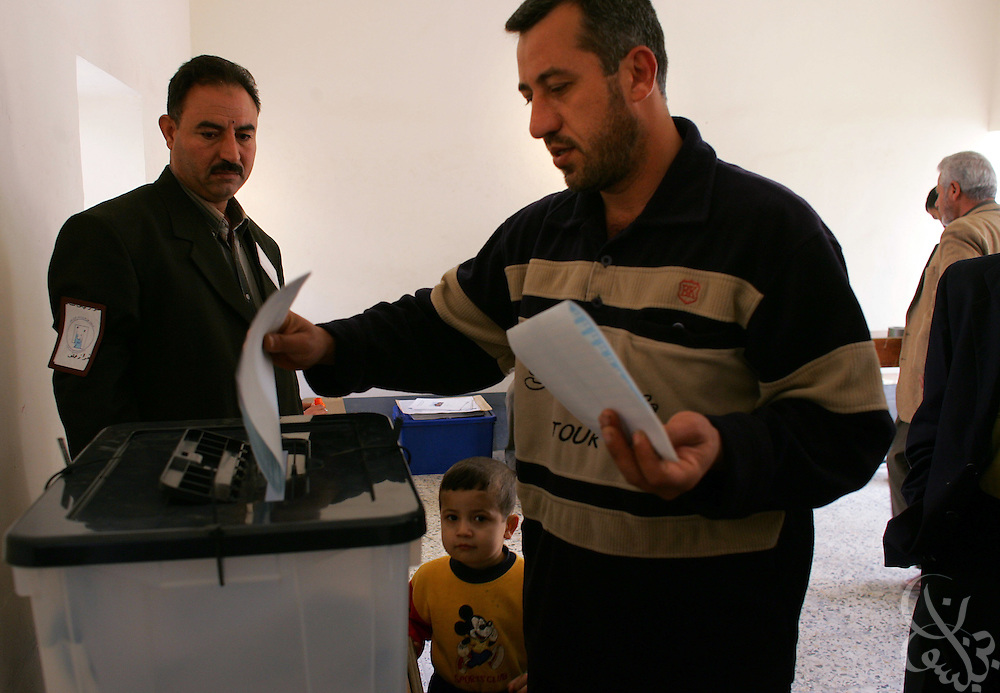 A Sunni boy watches as his father casts a ballot in the national Iraqi elections December 15, 2005 at the al Imam al Adel school in western Ramadi, Iraq. Turnout across Ramadi, capital of Anbar province and a restive Sunni insurgent stronghold, appears to be high, marking a huge contrast to the October referendum when there were very few votes cast.