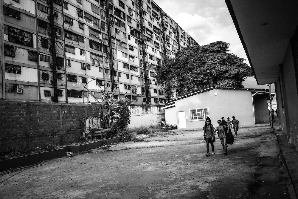 Children walk to music class with government housing in the background at the 23 de Enero nucleo, of the El Sistema music program. 23 de Enero slum is the stronghold of late socialist President, Hugo Chavez. It is where his armed, militant supporters live, and is indisputedly the heart of the Revolution in Venezuela.