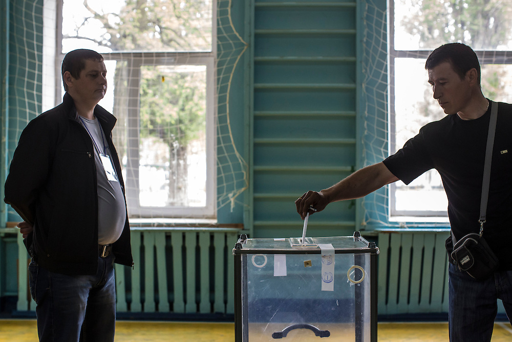 HARTSIZK, UKRAINE - MAY 11: A man casts his ballot at a polling station on May 11, 2014 in Hartsizk, Ukraine. A referendum on greater autonomy is being held after pro-Russian activists took over at least ten cities in the eastern part of the country in a bid for less control from the central government from Kiev. (Photo by Brendan Hoffman/Getty Images) *** Local Caption ***