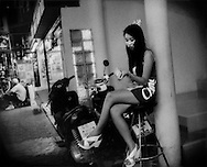 """Young woman, possibly a dancer, stationed at the entrance to a go-go bar to attract male customers on """"Walking Street"""" which is lined with go-go bars and clubs.   It becomes a pedestrian street at night packed with an international throng of Thai and foreign tourists, men and women and even some children.  Pattaya, Thailand."""