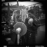 Asia, China, Beijing, Blurred black and white image of tourists standing in front of fan before posing for snapshots wearing Imperial era costumes at photo studio in the Forbidden City