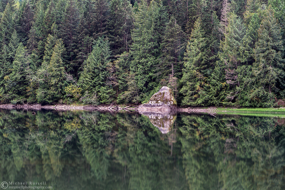 A large rock and the surrounding forest are reflected in Silver Lake near Hope, British Columbia, Canada. Photographed from the northeast end of  Silver Lake at Silver Lake Provincial Park near the exit of Silverhope Creek from Silver Lake.