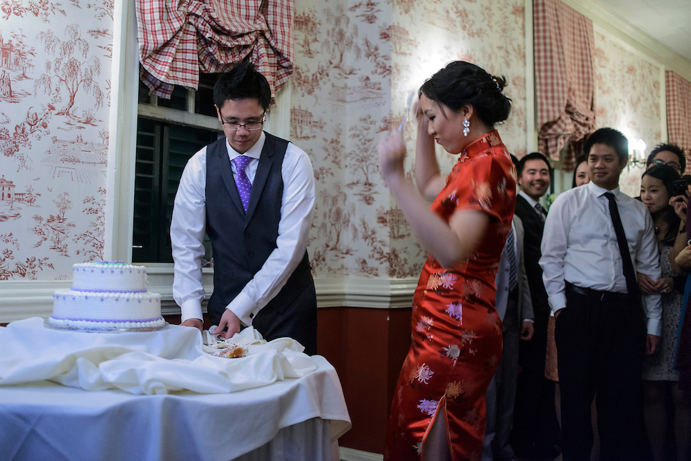 Photo by Matt Roth.Assignment ID: 30140754A..Evelyn Hsieh does a little dance while her new husband Michael Wong cuts the cake during their reception at the the Mount Vernon Inn, in Mount Vernon, Virginia on Saturday, April 06, 2013. Evelyn changed from her white wedding dress to a traditional red Chinese wedding dress.