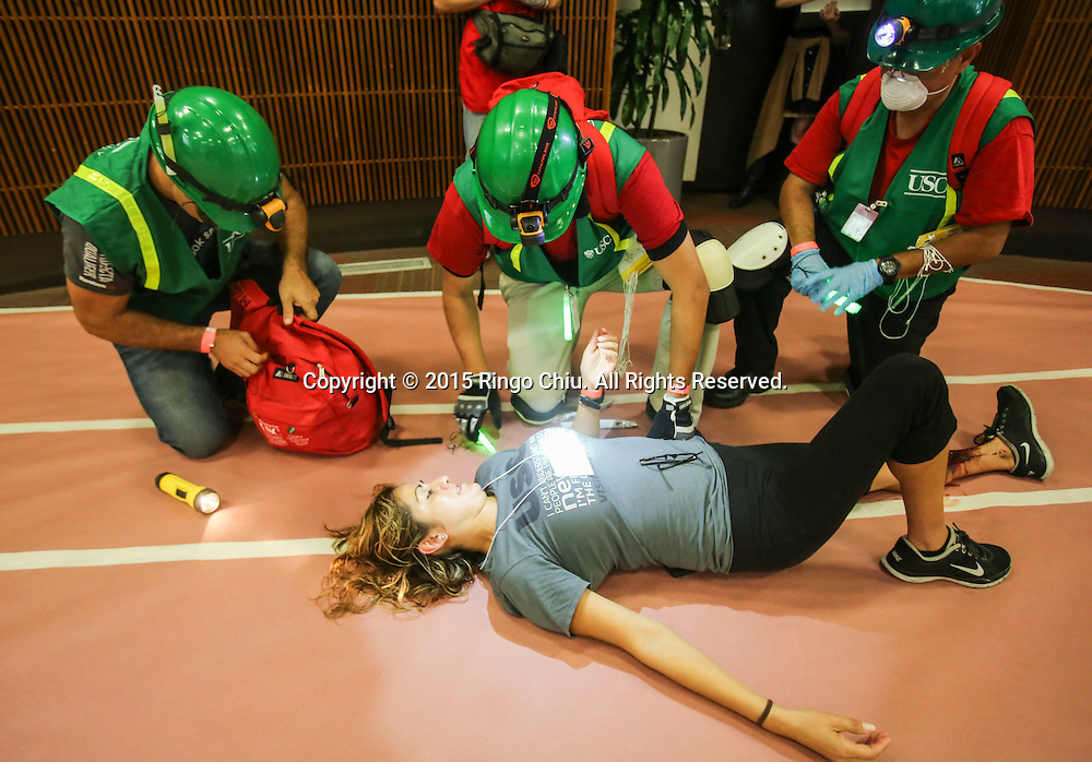 Rescuers give treatment to a mock victim during the annual Great California ShakeOut earthquake drill at Southern California University (USC) in Los Angeles on October 15, 2015. About 10.4 million Californian's registered to take part in the annual drill that asks participants to 'drop'' to the ground, take 'cover'' under a desk, table or other sturdy surface, and 'hold on'' for 60 seconds, as if a major earthquake were occurring.(Photo by Ringo Chiu/PHOTOFORMULA.com)