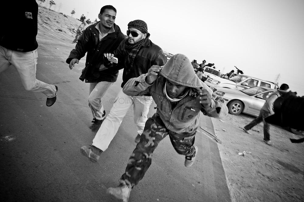 Des combattants rebelles fuient les bombardements de l'armée loyaliste, le 25 mars 2011 à une dizaine de kilomètres de la ville d'Aj Dabiya.