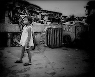 Young girl standing on bridge over fouled river lined with makeshift houses in Manila slum, Philippines.