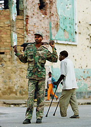 """An Angolan soldier known as """"Bernardo"""" walks through the destroyed town of Kuito as a man who lost his leg to a landmine walks on crutches behind him.  Angola's brutal 26 year-civil has displaced around two million people - about a sixth of the population - and 200 die each day according to United Nations estimates. .(Photo by Ami Vitale)"""