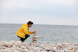 man on the beach piling up rocks by the ocean