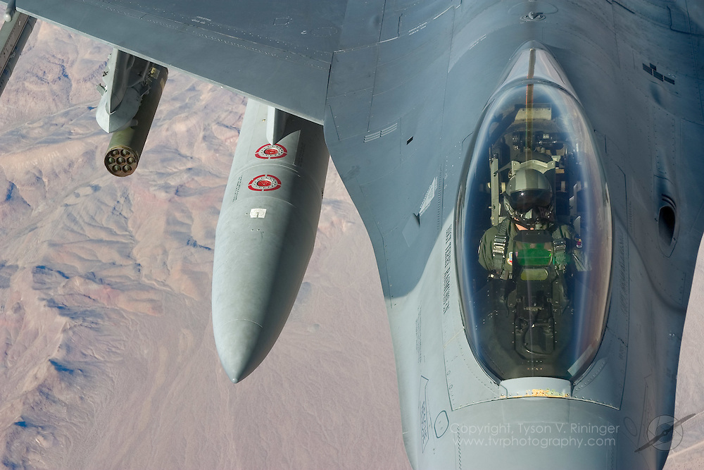 """A 'Blue Team' F-16 from the 388th Wing, 421st Fighter Squadron, the """"Black Widows"""", flies high above the Nevada desert during a training exercise. Taking a break from the action below the clouds, this F-16 from Hill Air Force Base prepares to take on fuel from an awaiting KC-135 Tanker from the Washington State Air National Guard."""
