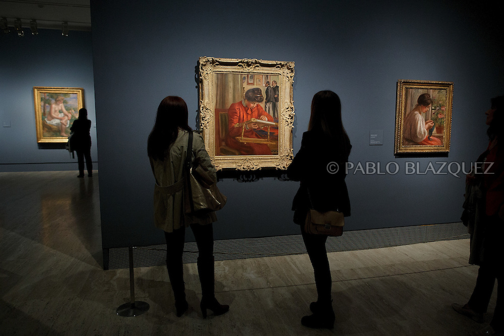 Members of the press look at Pierre Auguste-Renoir's work 'Christine Lerolle Embroidering', painted in 1895-1898 at the Museum Thyssen-Bornemisza on October 17, 2016 in Madrid, Spain. 'Renoir: Intimacy' features 78 works by French painter Renoir (1841-1919) borrowed from museums and collections from around the world and will be open to the public from October 18, 2016 to January 22, 2017 (© Pablo Blazquez)