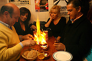 "Tourists share a grilled ""chourico"" (chorizo) at""Tasca do Chico"". This one of the typical spots were to see live perfomances of Fado music and were the audience can spontaneously participate and also ask to sing. It is located in  Bairro Alto neighborhood"