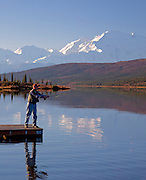 Alaska. Fly fishing from the canoe dock on Wonder Lake, enjoying the clam morning waters and Mt. McKinley as a back drop, Denali National Park.  (MR)