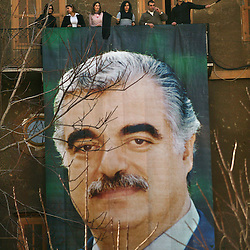 People are seen above a banner of former Prime Minister Rafik Hariri in Beirut, Lebanon, Feb. 21, 2005. Several thousand Lebanese gathered at the scene of the bombing that killed Hariri, afterward they to walked to his grave. The crowd demanded a Syrian pullout and an international probe into the assassination.