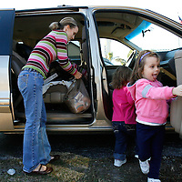 LEHIGH ACRES, FL -- January 23, 2009 -- Megan Brown of Lehigh Acres loads up her daughters Kayley, 2, left, and Sydney, 4, after picking up free bread and pastries for her family at the bread line at Faith Lutheran Church in Lehigh Acres, Fla., on Friday, January 23, 2009.  Lehigh Acres has become a symbol for the fallen American Dream - with only two years separating itself from housing market boomtown to a current landscape of abandoned developments and struggling businesses.