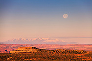 The full moon sets at sunrise over Utah's Canyonlands National Park and the Green River plateau, with Mount Pennell and Capitol Reef National Park in the distant background.<br /> <br /> WATERMARKS WILL NOT APPEAR ON PRINTS OR LICENSED IMAGES.<br /> <br /> Licensing: https://tandemstock.com/assets/58597476
