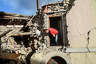 24 August 2016, Amatrice Italy - A man involved in searches for survivors in a house destroyed by earthquake at Amatrice.