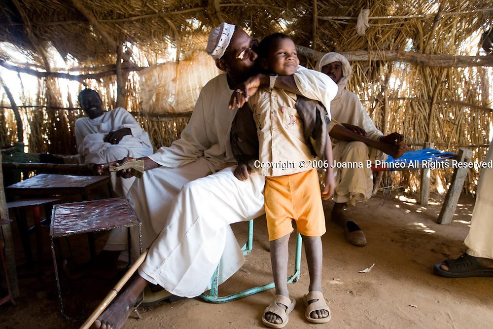 Camel broker Elsean Ahmed Naiem with his son Ali Mohammed Abo in a tea hut at the camel market in El Obeid, Sudan.