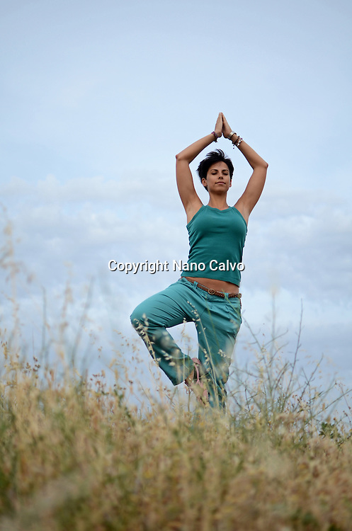 Young short haired woman doing tree yoga pose