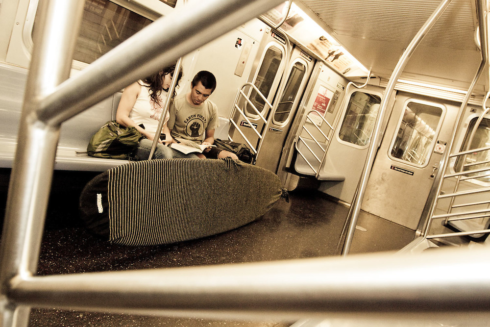 A surfer couple takes the L-Train back to Manhattan en route from Rockaway Beach, Queens, NY.