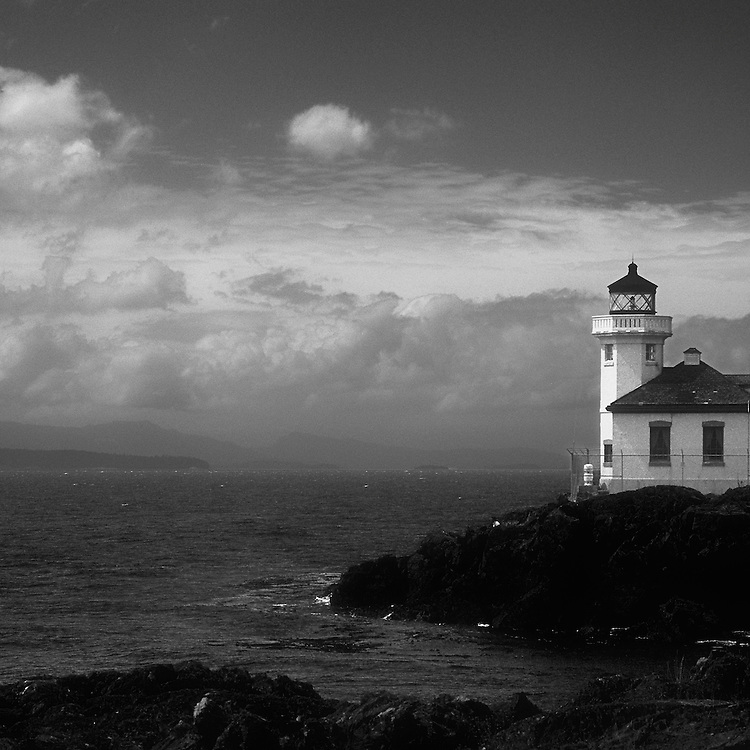 Black and white image of lighthouse on Alki Point, Washington. The furthest point west in the mainland United States. Lighthouse on the rocks jutting out into the Pacific Ocean. Dense rolling clouds on the horizon and black islands, rocky shoreline and mountains across the bay on the horizon. Pacific Northwest.