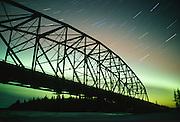 Alaska.  George Parks Highway.  Aurora Borealis over the Nenana River Bridge.