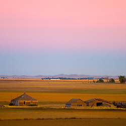 A colorful sun set splashes all sorts of hues into the sky over an old homestead on the plains of western Nebraska.