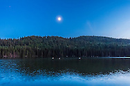 The quarter Moon reflected in the waters of Reesor Lake, Alberta in Cypress Hills Interprovincial Park, with three white pelicans floating by. Taken on July 5, 2014. This is with the 10-22mm Canon lens and Canon 60Da at ISO2000. This is a single 1.1 sec exposure at f/4. The Moon was in conjunction with Mars (right of Moon) and Spica (left of Moon).