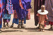 A little girl watches as the women dance.