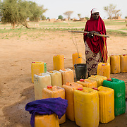 A woman preparing to carry two heavy containers of water home from a well refurbished by WaterAid in the village of Gadirga in the Commune of Soukoukoutan in the Dosso Region of Niger on 23 July 2013.
