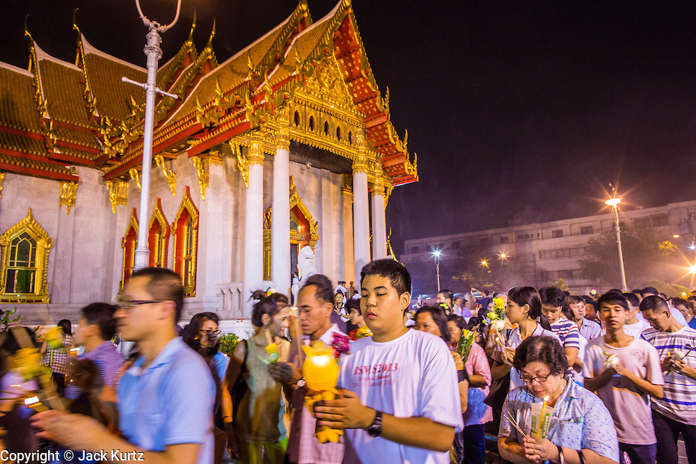 "25 FEBRUARY 2013 - BANGKOK, THAILAND: Thais participate in a candle light procession around Wat Benchamabophit Dusitvanaram (popularly known as either Wat Bencha or the Marble Temple) on Makha Bucha Day. Thais visit temples throughout the Kingdom on Makha Bucha Day to make merit and participate in candle light processions around the temples. Makha Bucha is a Buddhist holiday celebrated in Myanmar (Burma), Thailand, Cambodia and Laos on the full moon day of the third lunar month (February 25 in 2013). The third lunar month is known in Thai is Makha. Bucha is a Thai word meaning ""to venerate"" or ""to honor"". Makha Bucha Day is for the veneration of Buddha and his teachings on the full moon day of the third lunar month. Makha Bucha Day marks the day that 1,250 Arahata spontaneously came to see the Buddha. The Buddha in turn laid down the principles his teachings. In Thailand, this teaching has been dubbed the 'Heart of Buddhism'.      PHOTO BY JACK KURTZ"