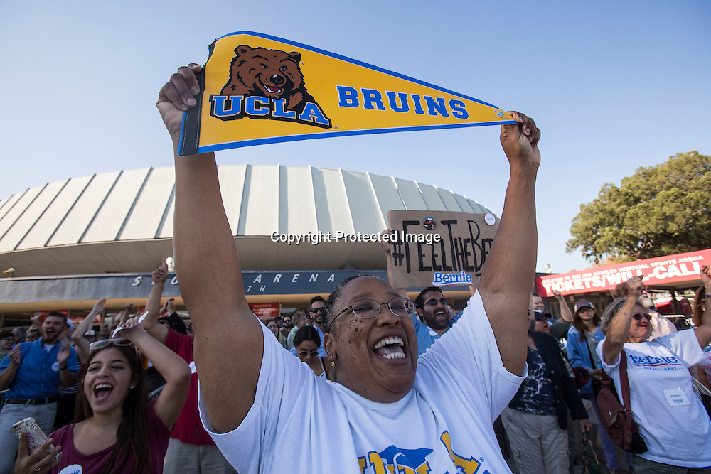 Teresa A. Pitts, of Los Angeles, holds up a UCLA flag before a rally for democratic presidential candidate Sen. Bernie Sanders, I-Vt., Monday, Aug. 10, 2015, at the Los Angeles Memorial Sports Arena in Los Angeles. (AP Photo/Ringo H.W. Chiu)