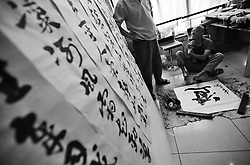 Chinese disabled artist Xi Fu (R ) practices calligraphy with his teacher Liu Shenwei in Daxing Arts Centre on the outskirts of Beijing, China 18 June 2013. At the age of 18, he joined a children's art class at an art centre and began to learn painting from art teacher Ren Zhijun, who was so taken by Xi Fu that he taught him for free. Another two teachers noticed his talent and started teaching him calligraphy. Xi Fu practiced for hours everyday even though his condition made it painful for him to remain in his writing position for long periods of time. It was however only three years later in 2003 that his teachers proclaim him good enough to make a living from his art. Xi Fu's story is one that tells of how strong determination and hard work overcame the difficulties of surviving in a society scant with infrastructure and support for the disabled and where they are often discriminated and sidelined.