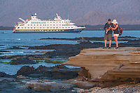 A couple enjoying photography in front of the Endeavour II at Puerto Egas on Santiago Island, Galapagos.