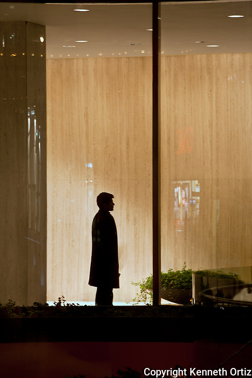 A photo of a lone business man waiting in the lobby of 9 west 57th Street building.