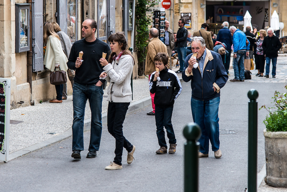 A family strolls in the village of Lourmarin, France. The son and grandfather are looking suspiciously at the camera.
