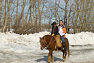 Young cowboy gives friend a ride on pony, Montana
