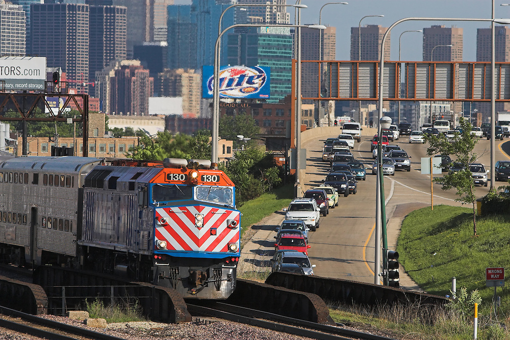 A Metra commuter train departs Chicago, IL, as rush hour traffic backs up on an adjacent interstate highway.