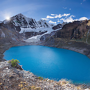 Turquoise Solteracocha lake (4120 m) under glaciers of Nevado Jirishanca (Icy Beak of the Hummingbird, 6126 m or 20,098 feet). Day 9 of 9 days trekking around the Cordillera Huayhuash in the Andes Mountains, near Llamac, Peru, South America. This panorama was stitched from 9 overlapping photos.