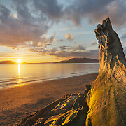 Sunset at Clayton Beach Larrabee State Park Washington. Chuckanut Formation sandstone rock formations in foreground, SanJuan Islands in the distance.
