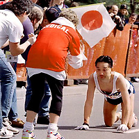 To the encouragment of race officials and helpers, a marathoner crawls the last 10 yards after collapsing just short of the finish line during the 1995 Vancouver Marathon. He succeeded in placing 75th.<br />