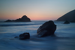 Waves break along rocks in Big Sur, California at sunset.