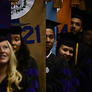 Law School graduates bearing banners for each academic school are ready to begin their ceremony procession.