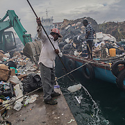 """Bengalese workers at the dump on Thilafushi island, the so-called """"rubbish island"""". Created to collect and burn all the garbage coming from the capital island Male and all the tourists resorts"""