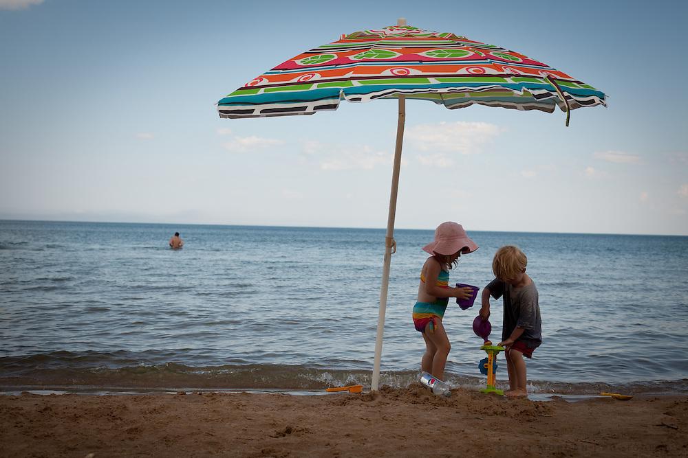 Children play under an umbrella on Lake Huron in Michigan.
