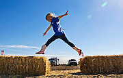 Cheyenne Olive, 7, of Nellis AFB jumps across hay bales following a Horses4Heroes ribbon-cutting ceremony and grand-opening event at Tule Springs on Thursday, March 06, 2014.  L.E. Baskow