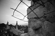 """A view down to an abandoned mosque in Shushi. This image is part of the photoproject """"The Twentieth Spring"""", a portrait of caucasian town Shushi 20 years after its so called """"Liberation"""" by armenian fighters. In its more than two centuries old history Shushi was ruled by different powers like armeniens, persians, russian or aseris. In 1991 a fierce battle for Karabakhs independence from Azerbaijan began. During the breakdown of Sowjet Union armenians didn´t want to stay within the Republic of Azerbaijan anymore. 1992 armenians manage to takeover """"ancient armenian Shushi"""" and pushed out remained aseris forces which had operate a rocket base there. Since then Shushi became an """"armenian town"""" again. Today, 20 yeras after statement of Karabakhs independence Shushi tries to find it´s opportunities for it´s future. The less populated town is still affected by devastation and ruins by it´s violent history. Life is mostly a daily struggle for the inhabitants to get expenses covered, caused by a lack of jobs and almost no perspective for a sustainable economic development. Shushi depends on donations by diaspora armenians. On the other hand those donations have made it possible to rebuild a cultural centre, recover new asphalt roads and other infrastructure. 20 years after Shushis fall into armenian hands Babies get born and people won´t never be under aseris rule again. The bloody early 1990´s civil war has moved into the trenches of the frontline 20 kilometer away from Shushi where it stuck since 1994. The karabakh conflict is still not solved and could turn to an open war every day. Nonetheless life goes on on the south caucasian rocky tip above mountainious region of Karabakh where Shushi enthrones ever since centuries."""